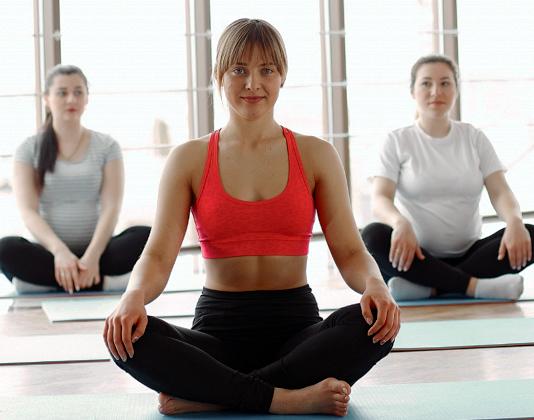 Tre donne praticano yoga sui tappetini