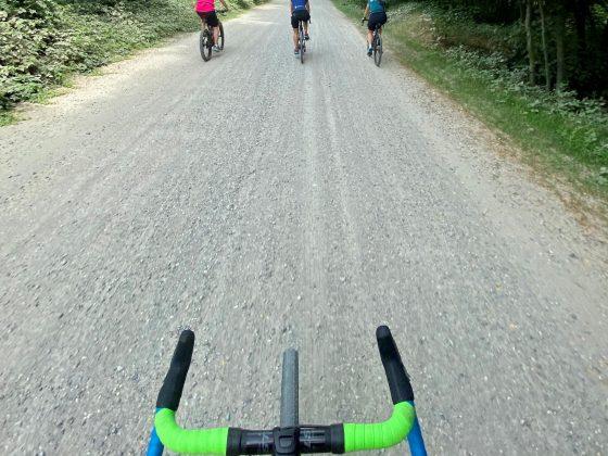 Copertina delle esperienze in gravel, vista manubrio bicicletta e davanti tre persone che percorrono una strada non asfaltata.